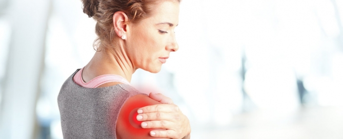 Portrait of sporty woman putting her hand on red spots on while has sport injury in her shoulder.